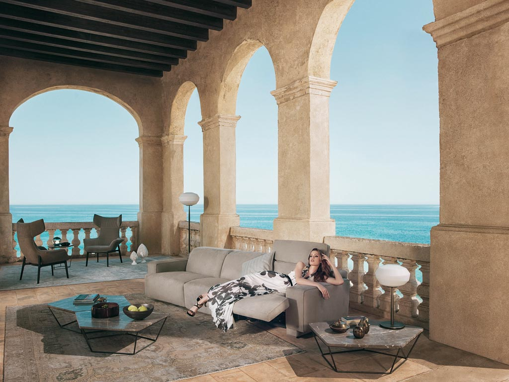 Natuzzi Italy . Couch Lake . The square and linear shapes and soft upholstery give rise to a surprising aesthetic result . Footrest and reclining headrest .