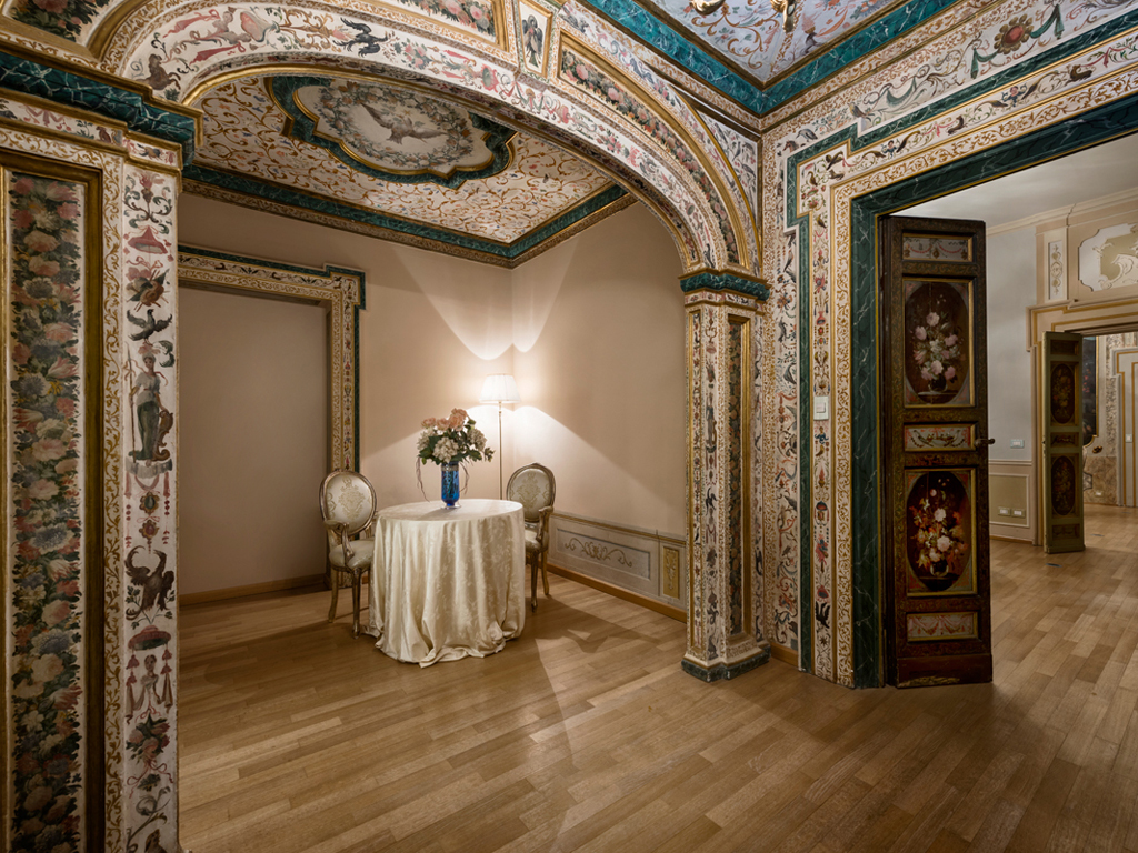Hotel Alla Posta dei Donini. Alcove room. Alla Posta dei Donini. Alcove room. The main floor, renovated in the mid-eighteenth century, still retains the classic row of lounges fitted with doors and paintings by Nicola Giuli in 1780.
