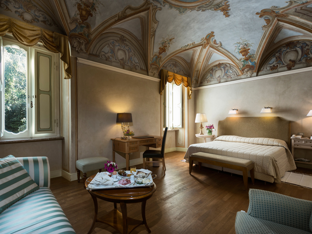 Hotel Alla Posta dei Donini. Bedroom with frescoed ceiling. Alla Posta dei Donini. The bedroom of the most prestigious historic residence. The ceiling, attributed to the school of Francesco Appiani, frescoed with architectural elements, floral elements and parts of the sky with angels. The room was once the dining room of Donini.