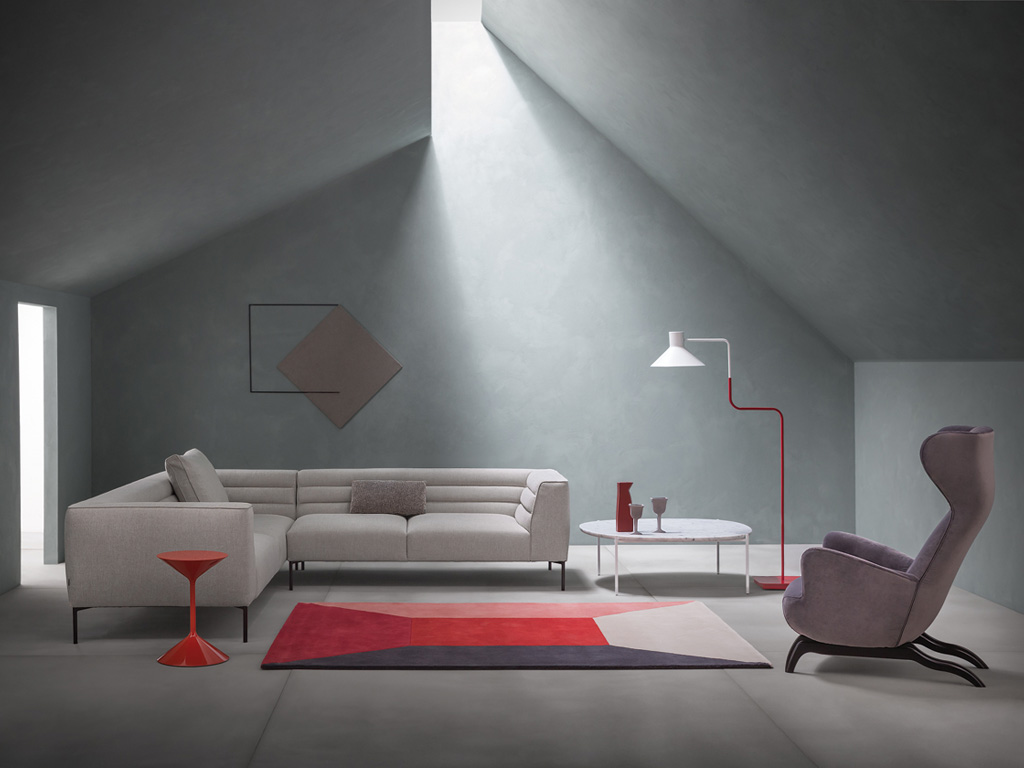 "Zanotta. In the picture, from left: red table ""Time"", designed by Prospero Rasulo; sofa composition ""Botero"" with back cushion in fabric, in black painted aluminum feet and fabric bearings, design Damian Williamson; table ""Niobe"", design Federica Capitani; armchair fabric ""Ardea"" (tribute to Carlo Mollino, 1944)."