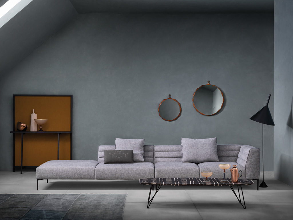 "Zanotta. In the picture, from left: screen with membrane-covered console shelf ""Shoji"", LucidiPevere design; composition ""Botero"" sofa with back cushions in fabric, in black painted aluminum feet, armrest stitching edge, back and cushions in canneté dark gray, bearing ""Cranes"" in cotton, design by Damian Williamson. Mirrors ""Raperonzolo"", Design by Atelier Oï; table ""Ink"", design by Emilio Nanni."