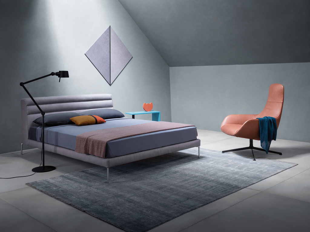 "Zanotta. ""Ruben"" bed in fabric, polished aluminum legs, design by Damian Williamson; table ""Basello"", Achille Castiglioni design; leather armchair ""Kent"", design by Ludovica + Roberto Palomba."